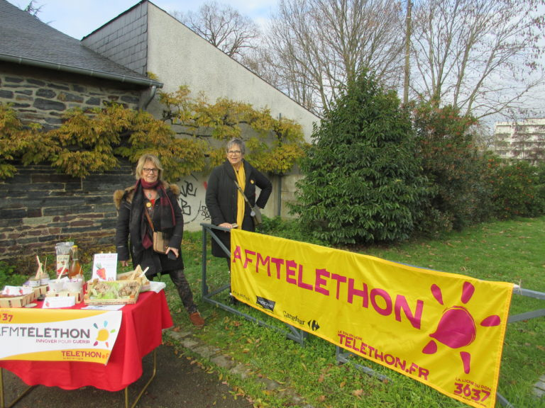 2 bénévoles devant la banderolle téléthon
